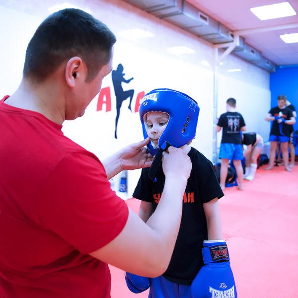 Уранбек помогает одевать боевое снаряжение ученику