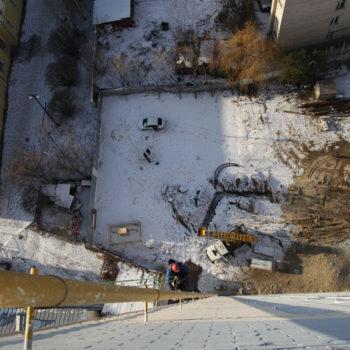 Работа альпиниста на монтаже осветительного оборудования на многоэтажке