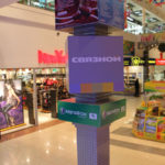 Многометровая рекламная конструкция в холле интерьера торгового центра